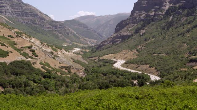 vídeos de stock, filmes e b-roll de view of road winding through canyon on hot summer day - provo