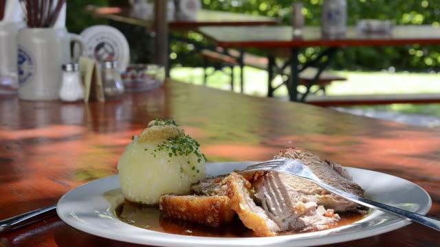 vídeos de stock e filmes b-roll de ms view of roast pork with dumpling / mainburg, bavaria, germany - porco