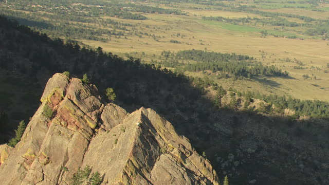 ms ds zo aerial view of rock climber on tower and landscape with shadowed backside of mountain in eldorado canyon in boulder county / colorado, united states - boulder rock bildbanksvideor och videomaterial från bakom kulisserna