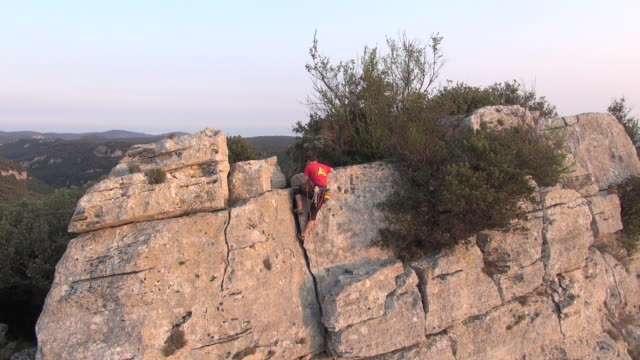 AERIAL view of rock climber scaling steep rock cliff to summit