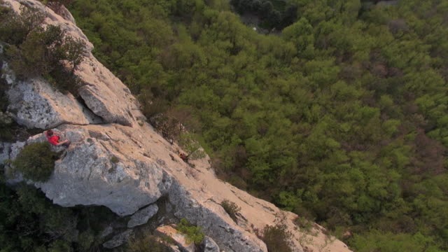 aerial view of rock climber scaling steep rock cliff to summit - one mid adult man only stock videos & royalty-free footage