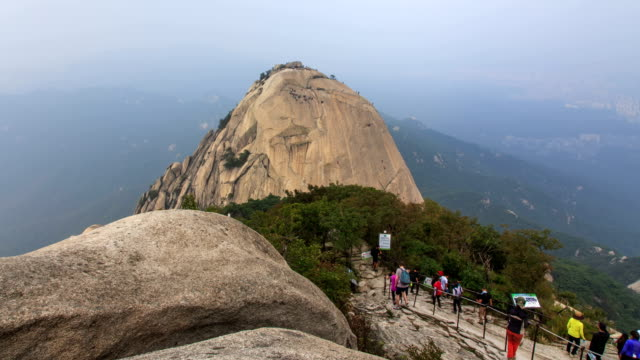 view of rock climbers climbing the rock face at mt. bukhansan national park (the most popular mountain in seoul) - rock face stock videos & royalty-free footage