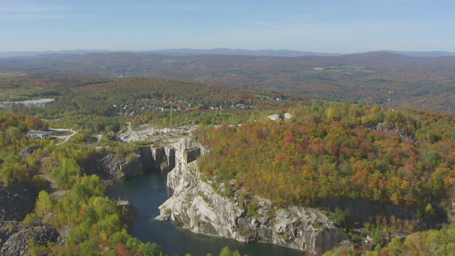 ws aerial pov view of rock of ages corporation with forest area / barre, washington county, vermont, united states - barre stock videos & royalty-free footage