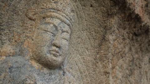 view of rock-carved buddhist image sitting cross-legged (korea treasure 199) at gyeongju sinseonam rock - male likeness stock videos & royalty-free footage