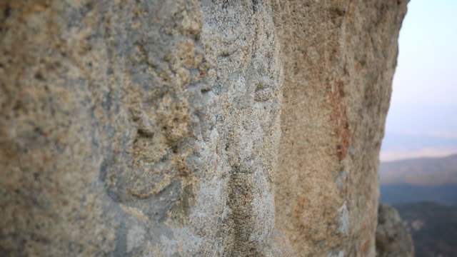 view of rock-carved buddhist image sitting cross-legged (korea treasure 199) at gyeongju sinseonam rock - figura maschile video stock e b–roll