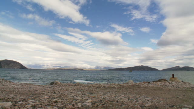 stockvideo's en b-roll-footage met ws view of rocky beach with fishing boat and mountains with whispy clouds in sky / torgat mtns, labrador, canada - wiese