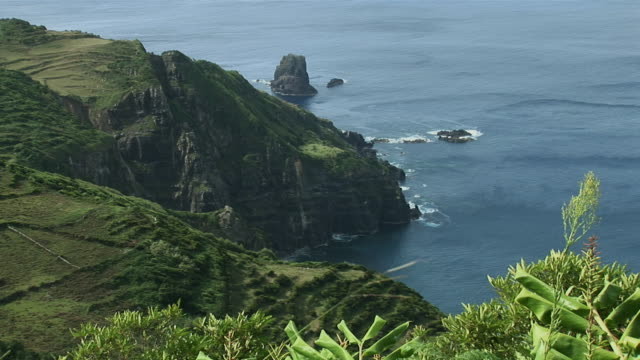 ws view of rocky coast with green flat fields above / mosteiro, flores island, azores, portugal - アゾレス諸島点の映像素材/bロール