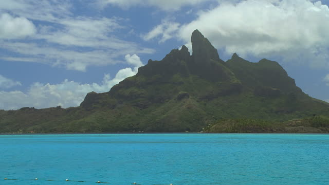ws view of rocky hill with blue background in foreground / bora bora, tahiti  - hill点の映像素材/bロール