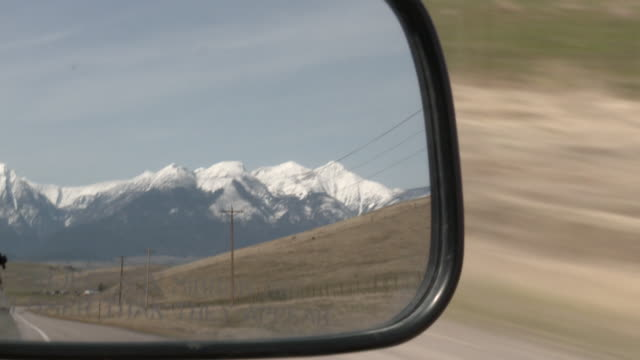 CU POV View of Rocky Mountains in rear view mirror / Missoula, Montana, United States