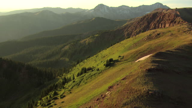 ws aerial view of rocky mountainsides and mountains during sunrise in pitkin county / colorado, united states - rocky mountains stock-videos und b-roll-filmmaterial