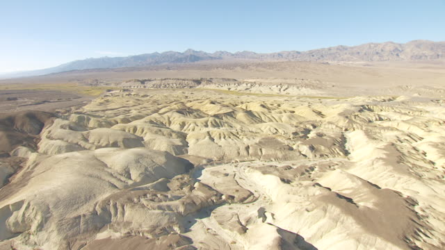 WS AERIAL POV View of rolling hills and dry stream beds in Death Valley with Funeral Mountains in background / California, United States