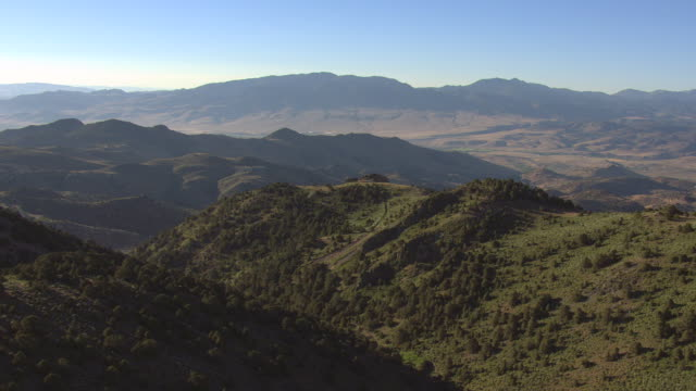 ws aerial view of rolling hills in virginia range in washoe county with mountains and clear skies / nevada, united states - mountain range stock videos & royalty-free footage