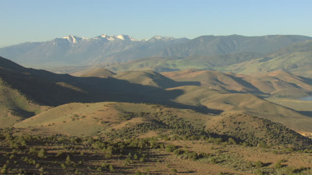 ws aerial view of rolling hills in virginia range in washoe county with mountains in and clear skies / nevada, united states - mountain range stock videos & royalty-free footage