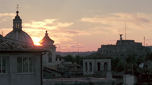 WS View of rooftops and skyline with partial silhouette Large dome of Church visible and sun is low in sky / Rome, Italy