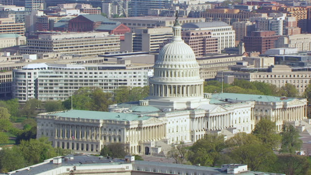 WS TS AERIAL POV View of rotate around US Capitol building and cityscape / Washington DC, United States