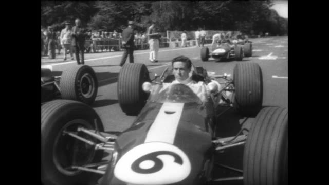 View of Rouen in France / crowd in stands before Gran Prix for Formula 2 cars / CU driver Graham Hill / driver Jack Brabham pulls helmet over head /...