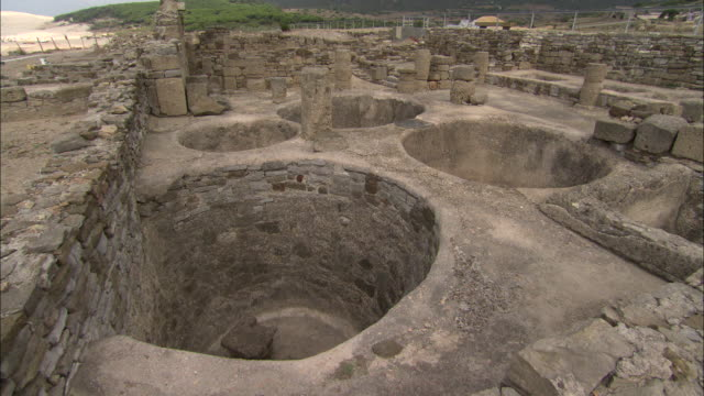 view of round pits in baelo claudia (ancient roman town) in cadiz, spain - foro video stock e b–roll
