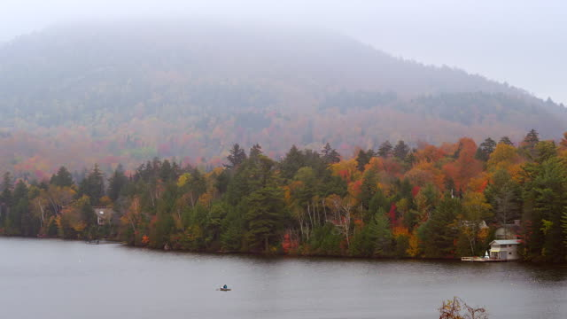 ws view of row boat crossing lake with foliage and mountains / lake placid, new york, united states - lake placid town stock videos and b-roll footage