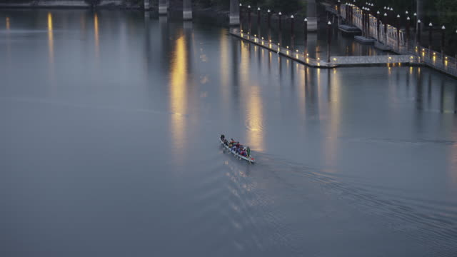 ws tu view of row boat paddles up willamette river rose garden coliseum in rose quarter / portland, oregon, united states  - river willamette stock videos & royalty-free footage