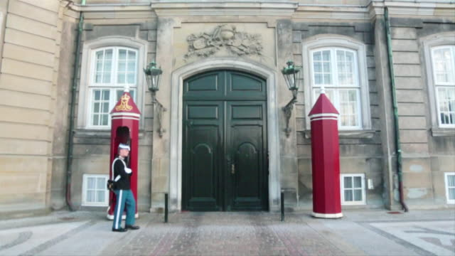 ws slo mo view of royal guard walking in front of amalienborg, passing two guard houses / copenhagen, denmark - 歩兵点の映像素材/bロール