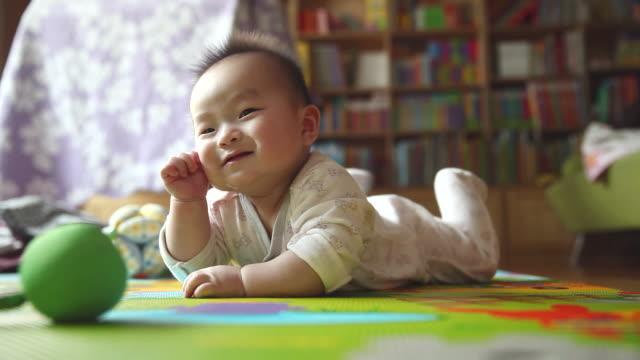 WS View of Rubbing eyes Korean baby lying on stomach / Jeju, Jeju-do, South Korea