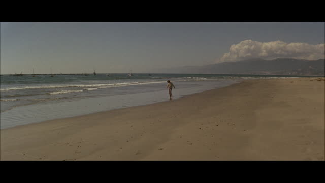 ws pan view of running girl on wide beach few small boats in background - carefree stock videos & royalty-free footage