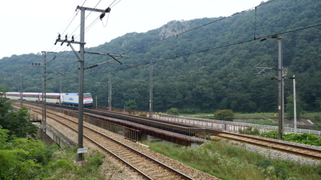 view of running mugunghwa train up on the honam line for dugyecheon stream in daejeon - railway bridge stock videos & royalty-free footage