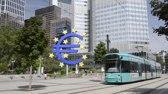 WS View of running tram in front of euro sign at European Central Bank with moving people / Frankfurt am Main, Hesse, Germany