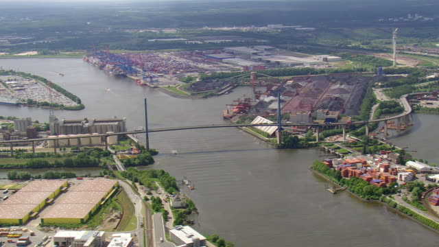 WS AERIAL View of running vehicles on suspension bridge and port near river with ship / Germany