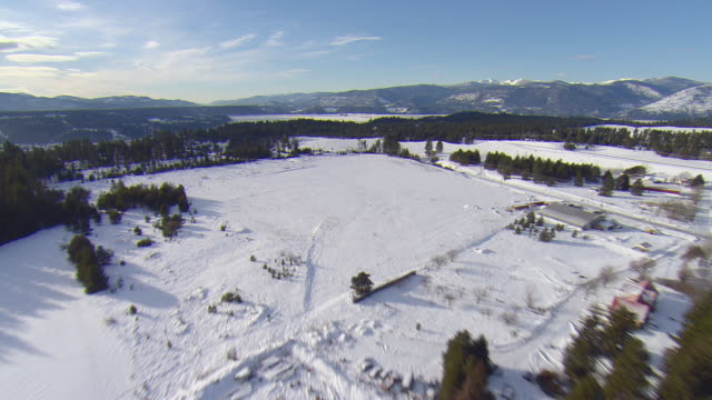 ws aerial view of rural bonners ferry, idaho with snow covered peaks of selkirk mountains / bonner's ferry, idaho, united states - マニトバ州点の映像素材/bロール