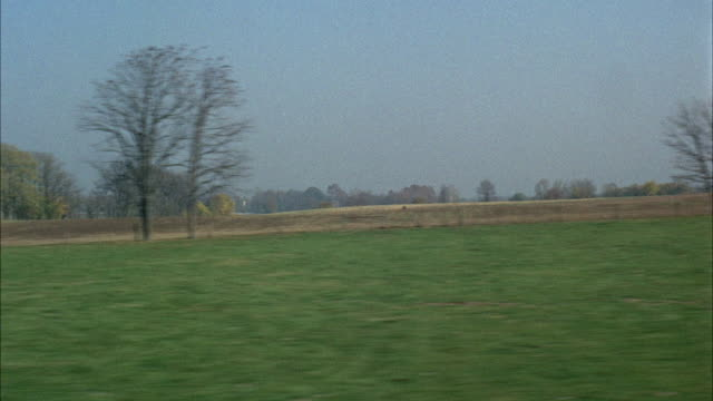 WS POV View of rural landscape from moving vehicle / Kentucky, USA