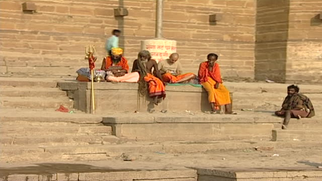 view of sadhus sitting on a ghat. a hindu religious symbol, a trishula or trident rests against a step. the ghats are used for ritual ablutions and... - religious symbol stock videos & royalty-free footage