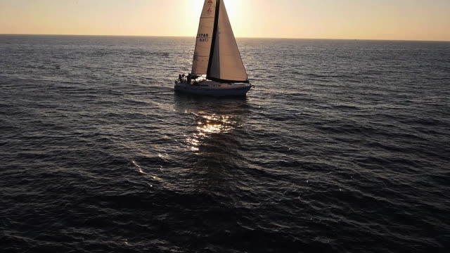 WS AERIAL POV TS SLO MO View of Sailboat sailing on ocean into sunset / Newport Beach, California, United States