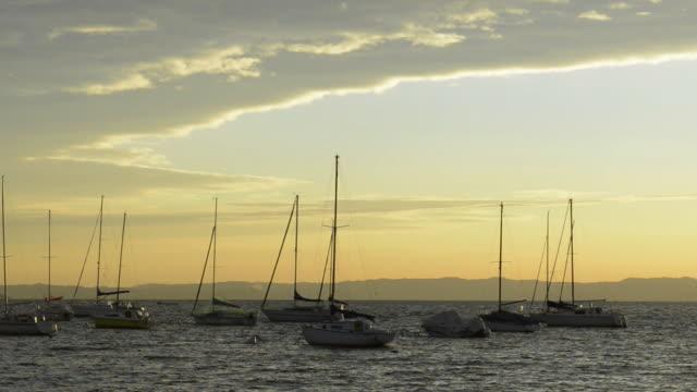 ms view of sailing boats moored on lake garda at sunset / bardolino, verona, italy - moored stock videos & royalty-free footage