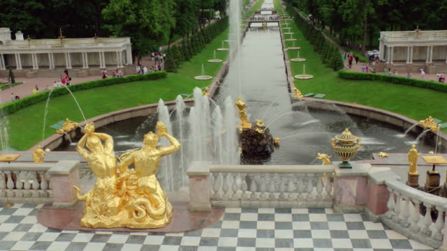 WS View of samson Fountain and Sea Channel with tourist walking in Peterhof palace Summer Garden / St. Petersburg, Russia