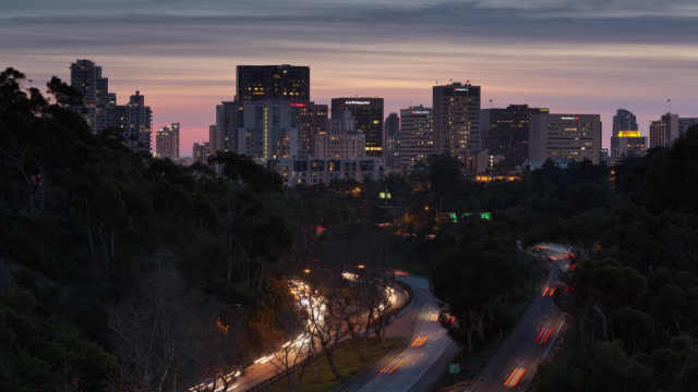 T/L View of San Diego skyline at night with traffic in the foreground / San Diego, California, USA
