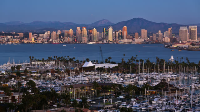 T/L View of San Diego skyline with marina in foreground at dusk / San Diego, California, USA