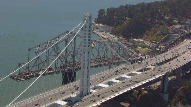ms aerial pov view of san francisco-oakland bay bridge (new bridge tower & old bridge missing section) / san francisco, california, united states - サンフランシスコ・オークランド・ベイブリッジ点の映像素材/bロール