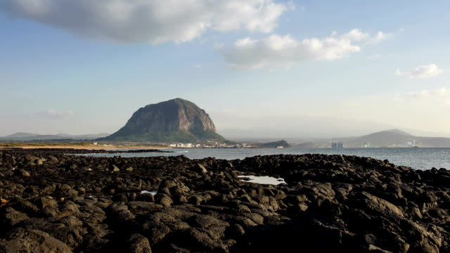 view of sanbangsan mountain and basalt beach - igneous stock videos & royalty-free footage