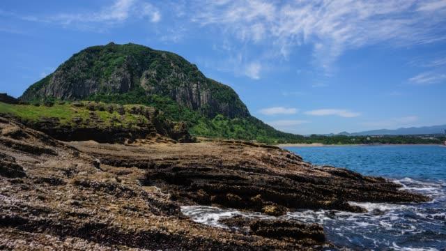 vídeos de stock, filmes e b-roll de view of sanbangsan mountain over yongmeori beach(it looks as if a dragon's head) in seogwipo, jeju island - ponto de referência natural
