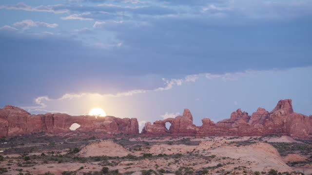 TL View of sandstone arches with full moon rising / Moab, USA