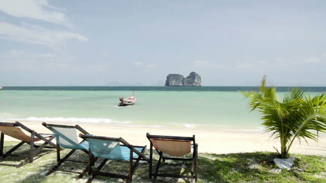 ws view of sandy beach, lounge chairs, long tail boat and limestone rock in sea, marine national park / ko hai, krabi, thailand - sessel stock-videos und b-roll-filmmaterial