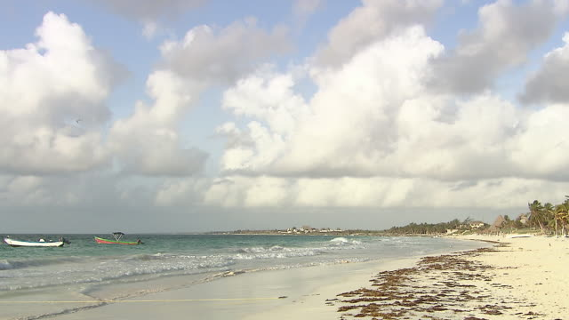 WS View of Sandy beach near Tulum, hotel complexes and small fishing boats berthed in Caribbean sea / Tulum, Quintana Roo, Mexico