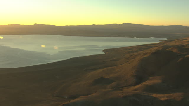 ws aerial pan view of sandy hills and pyramid lake at sunrise / nevada, united states - hügelkette stock-videos und b-roll-filmmaterial