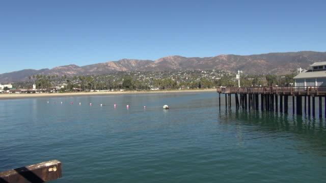 view of santa barbara harbor and mountains - サンタイネス点の映像素材/bロール