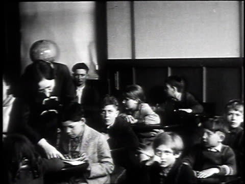 view of school exterior / teacher helping student / students reading in class / small girl sitting on man's lap reading - 1930 stock-videos und b-roll-filmmaterial