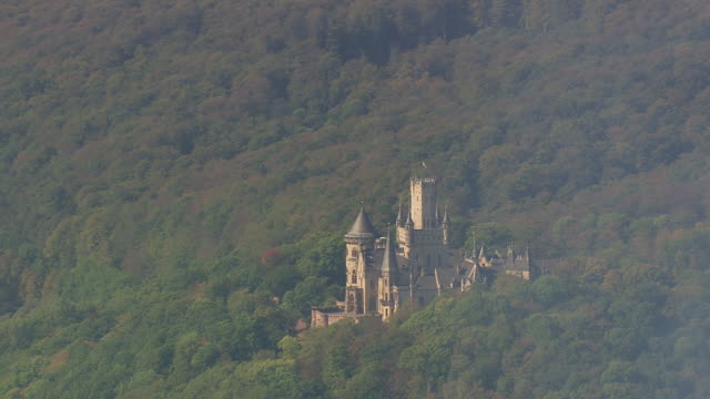 ws aerial view of schwarzburg castle high above valley and surrounded by wooded mountains with farm field / germany - schlossgebäude stock-videos und b-roll-filmmaterial