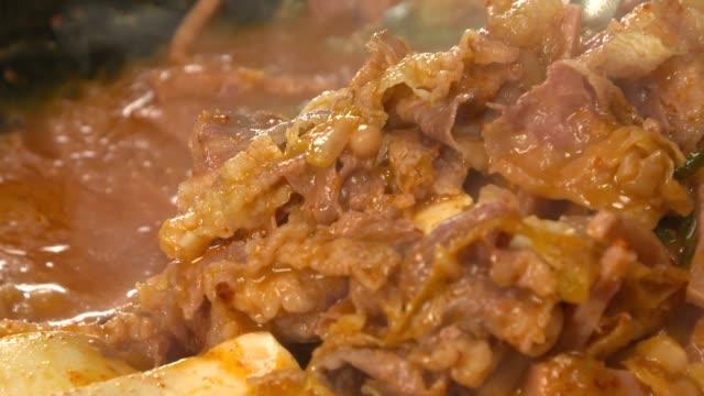 view of scooping up budae jjigae(korean style sausage stew) with chadolbaegi(korean style beef brisket) with ladle - ladle stock videos & royalty-free footage