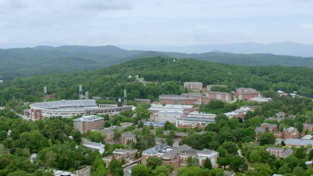 ws aerial pov view of scott stadium with cityscape, forest area in background / charlottesville, virginia, united states - university of virginia stock videos & royalty-free footage