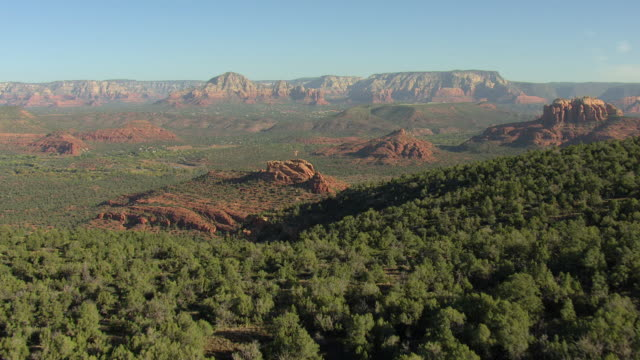 vídeos de stock e filmes b-roll de ws aerial view of scrubs to reveal large red rock formations / sedona, arizona, united states  - arenito